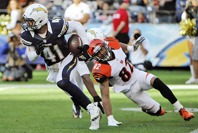 San Diego Chargers defensive back Corey Lynch (41) runs upfield after grabbing an interception as Cincinnati Bengals wide receiver Marvin Jones, right, watches during the second half of an NFL football game, Dec. 2, in San Diego. Lynch is among several professional football players who are showing it's possible to live and share their Christian faith in a powerful way without being as open or forthright as players like Tim Tebow or Ray Lewis.