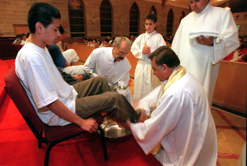Father Hernando Diaz (lower right) washes the feet parishoner during Maundy Thursday night service in preparation of Easter, April 1, 1999, at Sacred Heart Church. (Chuck Wing, Deseret News)