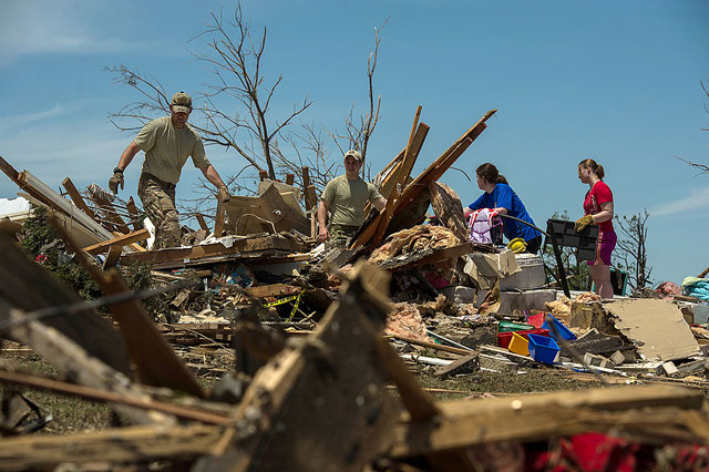Capt. Van Blaylock (left to right) and Senior Airman Joshua Jacobs help residents Alyson Tinney and Elise Hopkins search through the debris looking for salvageable items May 22, 2013, in Moore, Okla. An EF-5 tornado, with winds reaching at least 200 mph, traveled for 20 miles, leaving a two-mile-wide path of destruction, leveling homes, crushing vehicles, and killing more than 20 people May 20. More than 115 Oklahoma National Guard members have been activated to assist in the rescue and relief efforts. Jacobs is a joint terminal attack controller assigned to the 146th Air Support Operations Squadron. (U.S. Air Force photo by Staff Sgt. Jonathan Snyder)