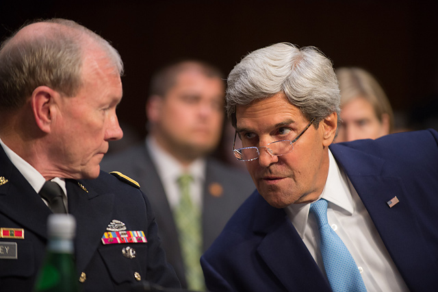 Secretary of State John Kerry speaks with Chairman of the Joint Chiefs of Staff Martin E. Dempsey during a Senate Foreign Relations Committee hearing at the Hart Senate Office building in Washington D.C. Sept. 3, 2013. President Barack H. Obama is seeking congressional approval for a limited military strike in Syria in response to their government's alleged use of chemical weapons. Department of Defense Photo by Mass Communication Specialist 1st Class Daniel Hinton.