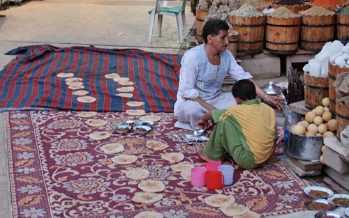 Vendor preparing 'aish (bread) for other vendors breaking their fast as 6PM approaches during Ramadam