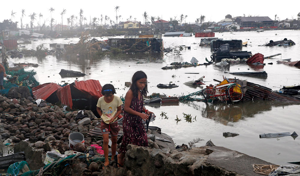 Residents walk near vehicles and debris floating on a river after Super Typhoon Haiyan devastated Tacloban city in central Philippines November 10, 2013. One of the most powerful storms ever recorded killed at least 10,000 people in the central Philippines province of Leyte, a senior police official said on Sunday, with coastal towns and the regional capital devastated by huge waves. Super typhoon Haiyan destroyed about 70 to 80 percent of the area in its path as it tore through the province on Friday, said chief superintendent Elmer Soria, a regional police director. REUTERS/Erik De Castro (PHILIPPINES - Tags: DISASTER ENVIRONMENT) - RTX157BX