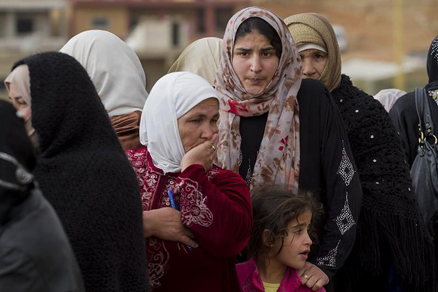 Archived Photo: Exhausted and uncertain about the future, a line of Syrian women and a young girl queue to register at an impromptu registration centre set up by UNHCR and partners just outside Arsal, Lebanon.  UNHCR/ M. Hofer/ November 2013